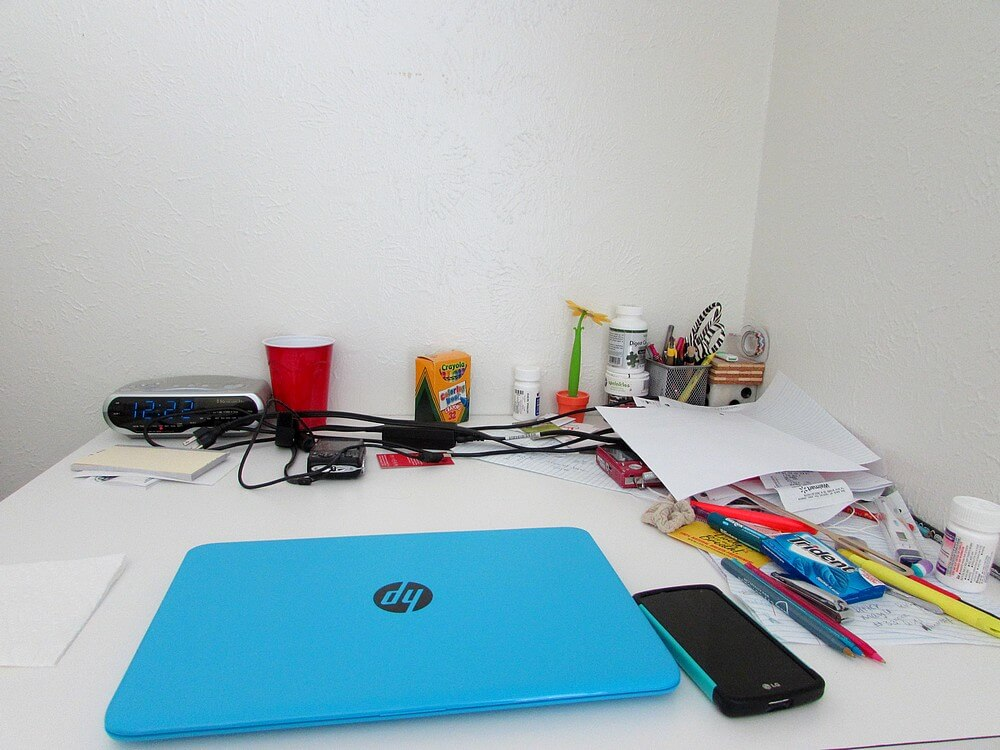 My desk with various paraphernalia, namely a blue laptop, box of Crayola crayons, two point-and-shoot cameras, papers, pens