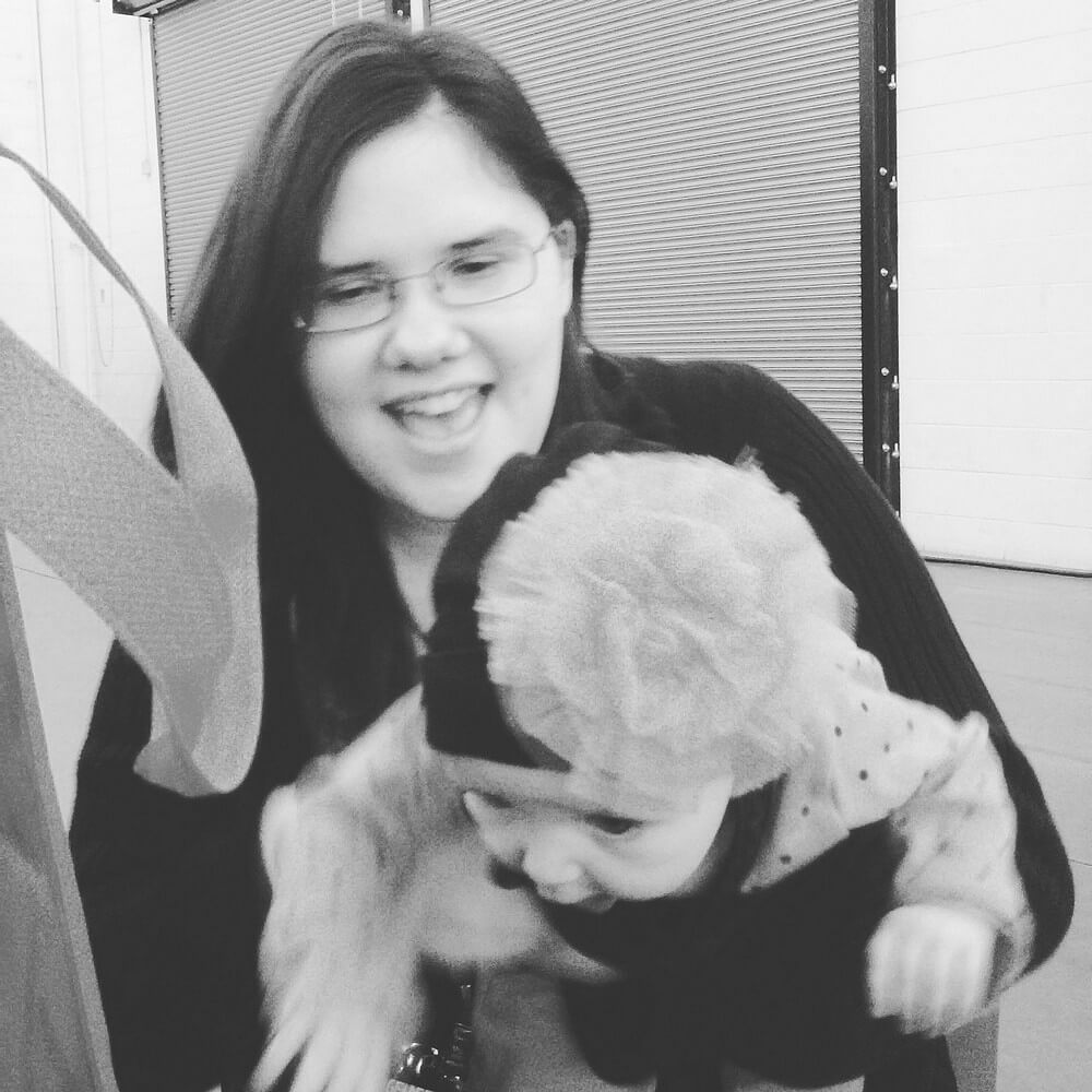 Black-and-white photo of my baby cousin Solara and I, with her leaning forward and me laughing mid-capture. It's a blooper.