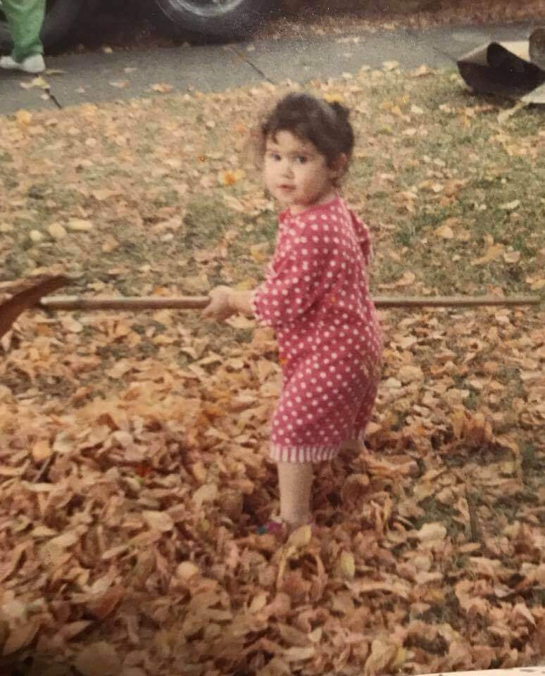 Toddler in pink romper holding a rake, surrounded by leaves