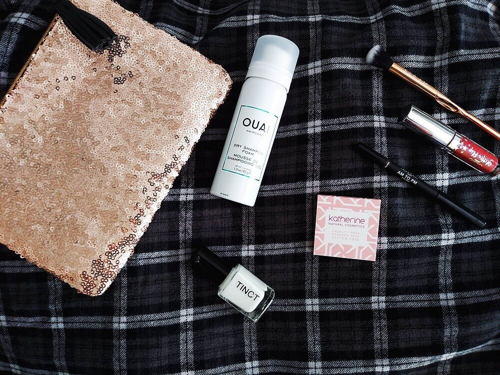Cosmetics (listed in caption) atop a black-and-white Madras flannel top