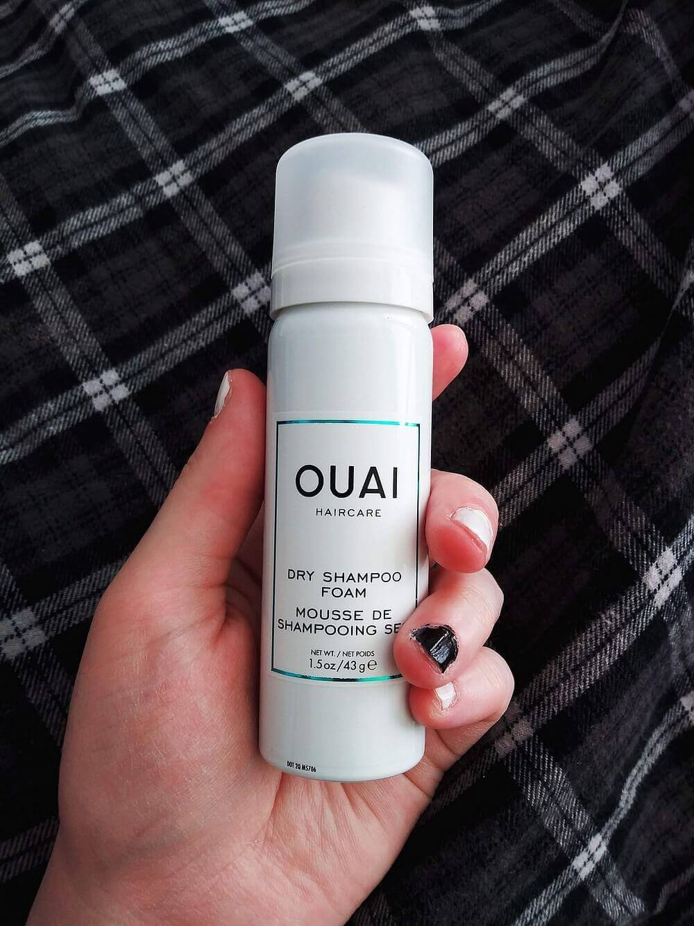 A canister of OUAI dry shampoo form in a hand; background is black-and-white Madras flannel top