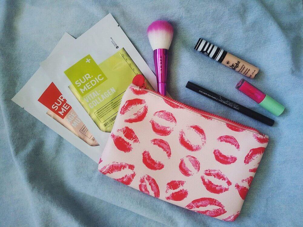 Blue jean background; pink lipstick lip pattern bag; contents of bag (listed below) beside and atop bag