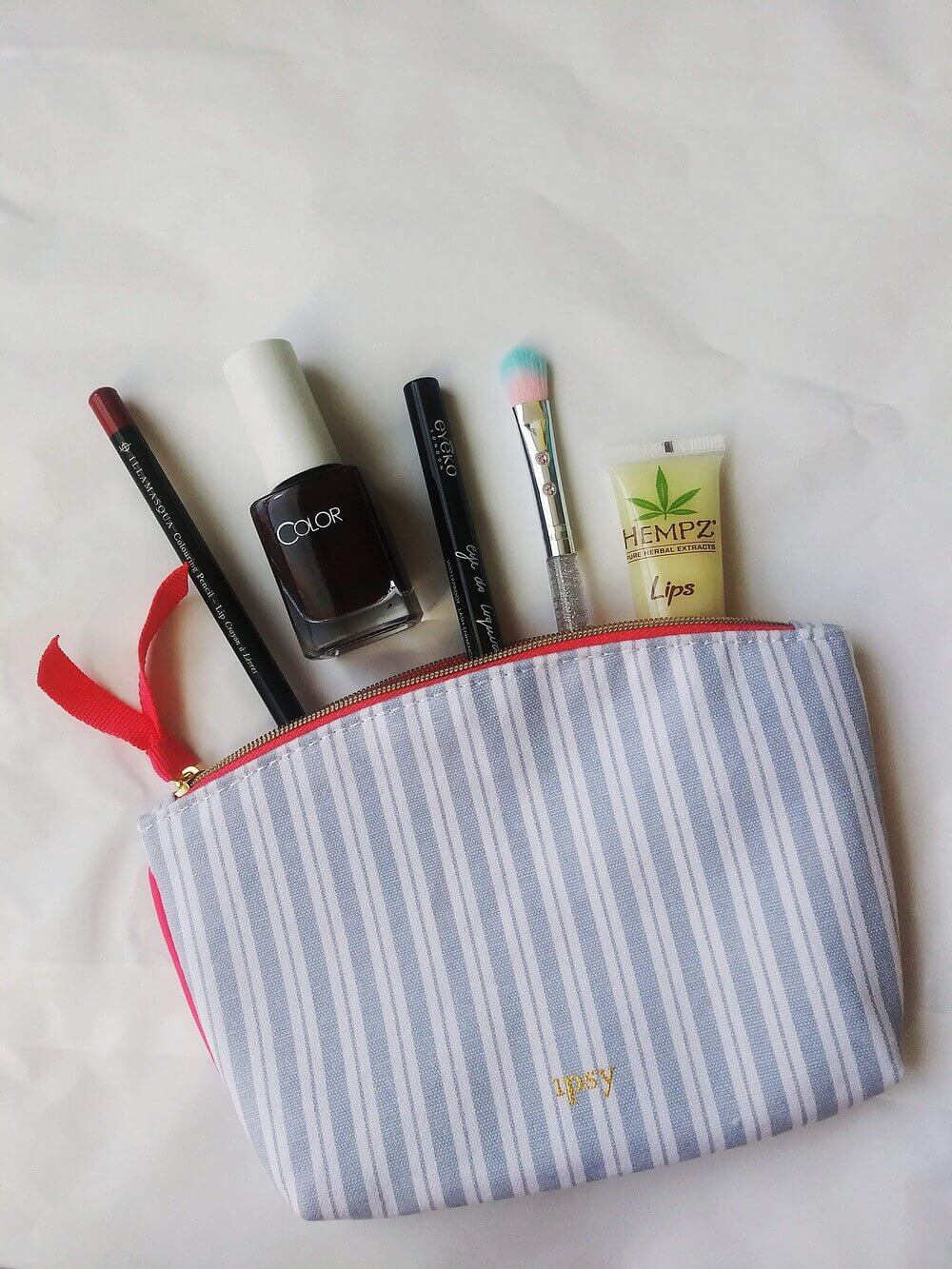 Contents (described in headers below) partially inside a striped cosmetic bag lined with hot pink