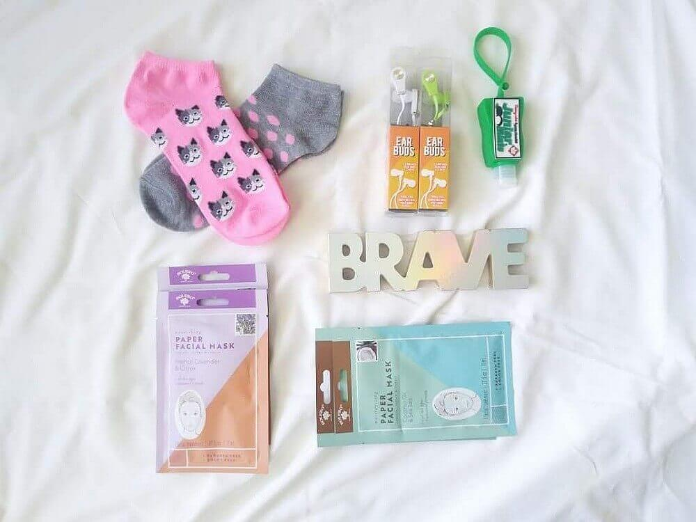 """Two pairs of socks (pink & grey polka dots, and white/grey cats on pink); wooden """"BRAVE"""" four paper facial masks; 2 pairs of ear bugs; Junior Mints®-scented hand sanitizer in a green holder"""
