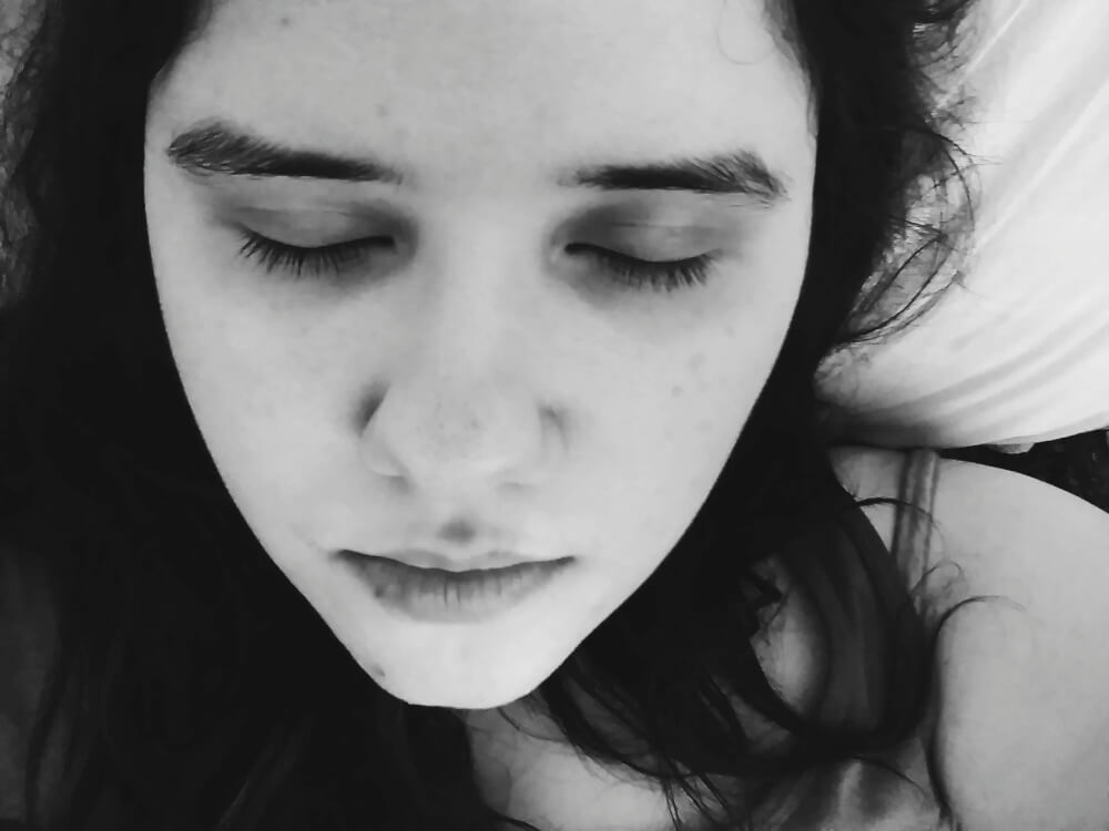 Black-and-white close-up selfie of face; eyes closed