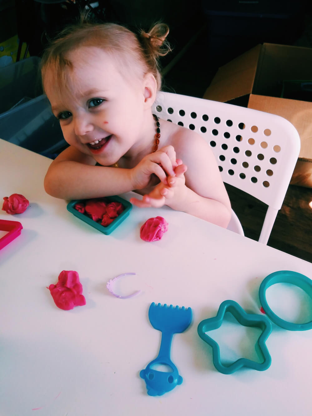 Caucasion toddler looking at photographer and giggling, while holding Playdough in hands