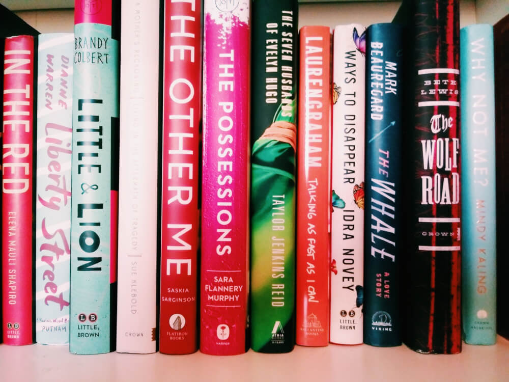 Vivid, bright spines of hardcover books on a white shelf, in alphabetical order