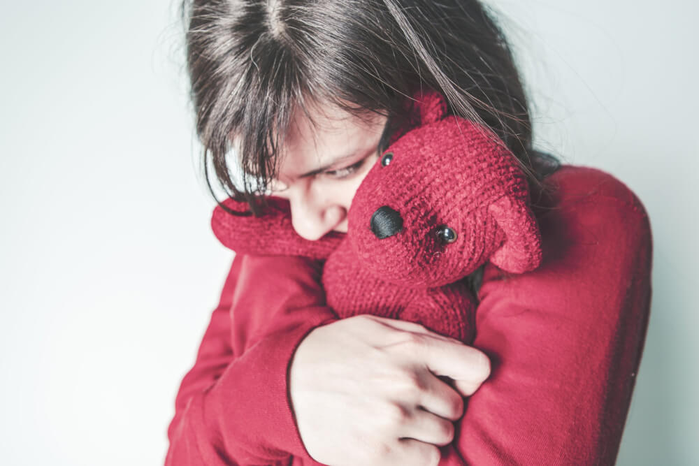 Long-haired child in red sweater holding red bear