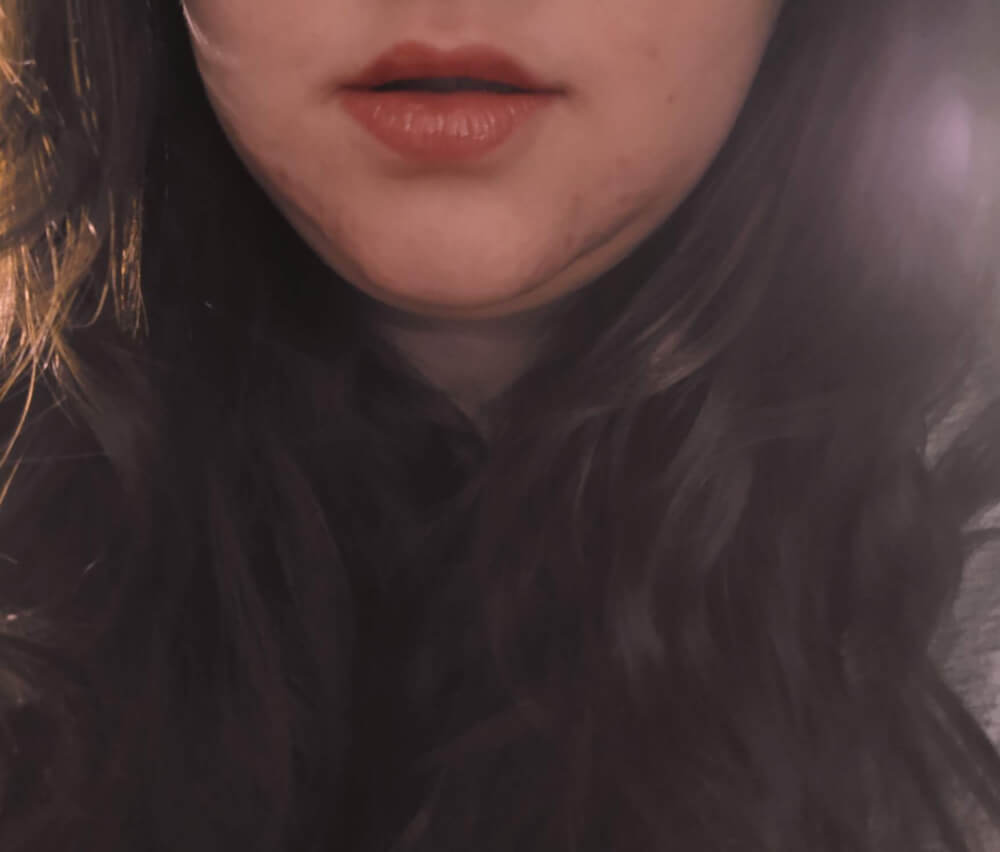 Lips, chin and hair under a soft filter; faceless