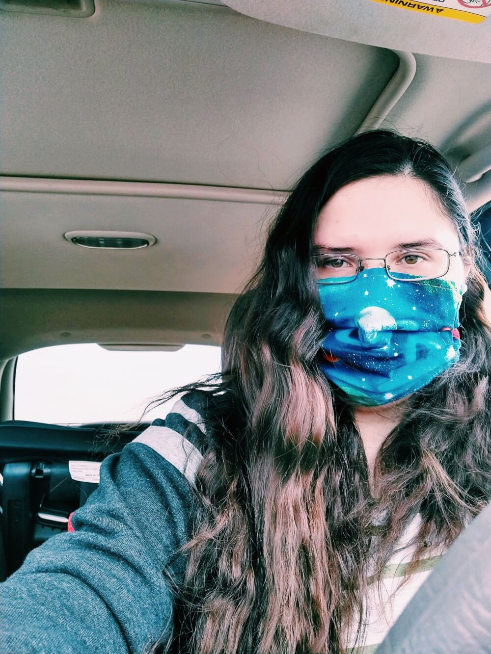 Selfie of me wearing a planetary mask, with wavy hair, in my car