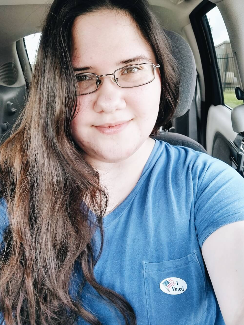"""Car selfie in blue top with """"I voted"""" sticker and wavy hair"""