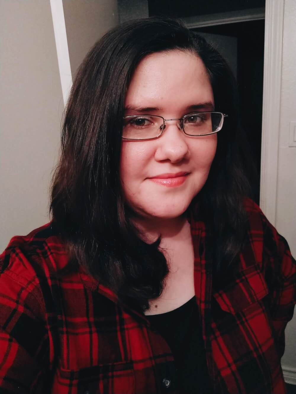 Selfie of me in glasses, a small smile, short hair, red plaid flannel