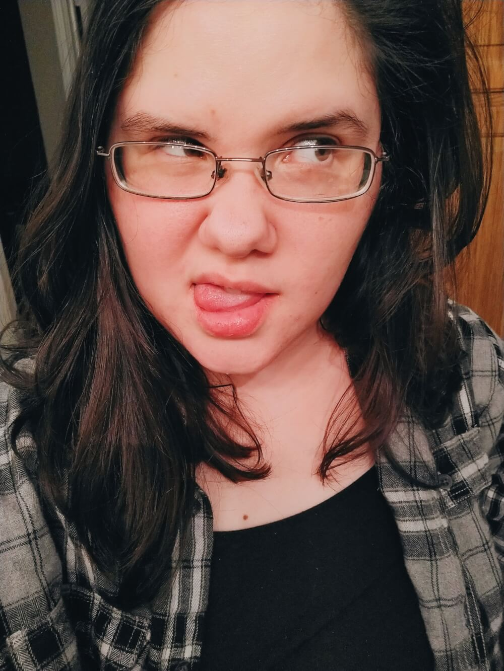 Silly selfie in black plaid flannel with tongue out