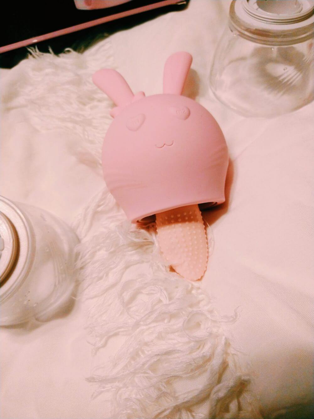 Pink rabbit head-shaped tongue vibrator; eyes are hearts and left ear has a bow decoration