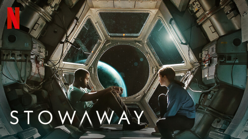 Black man and white woman sitting inside spaceship window looking out over Earth