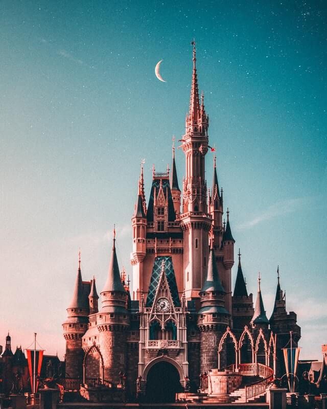 Walt Disney castle before cotton candy sky and crescent moon