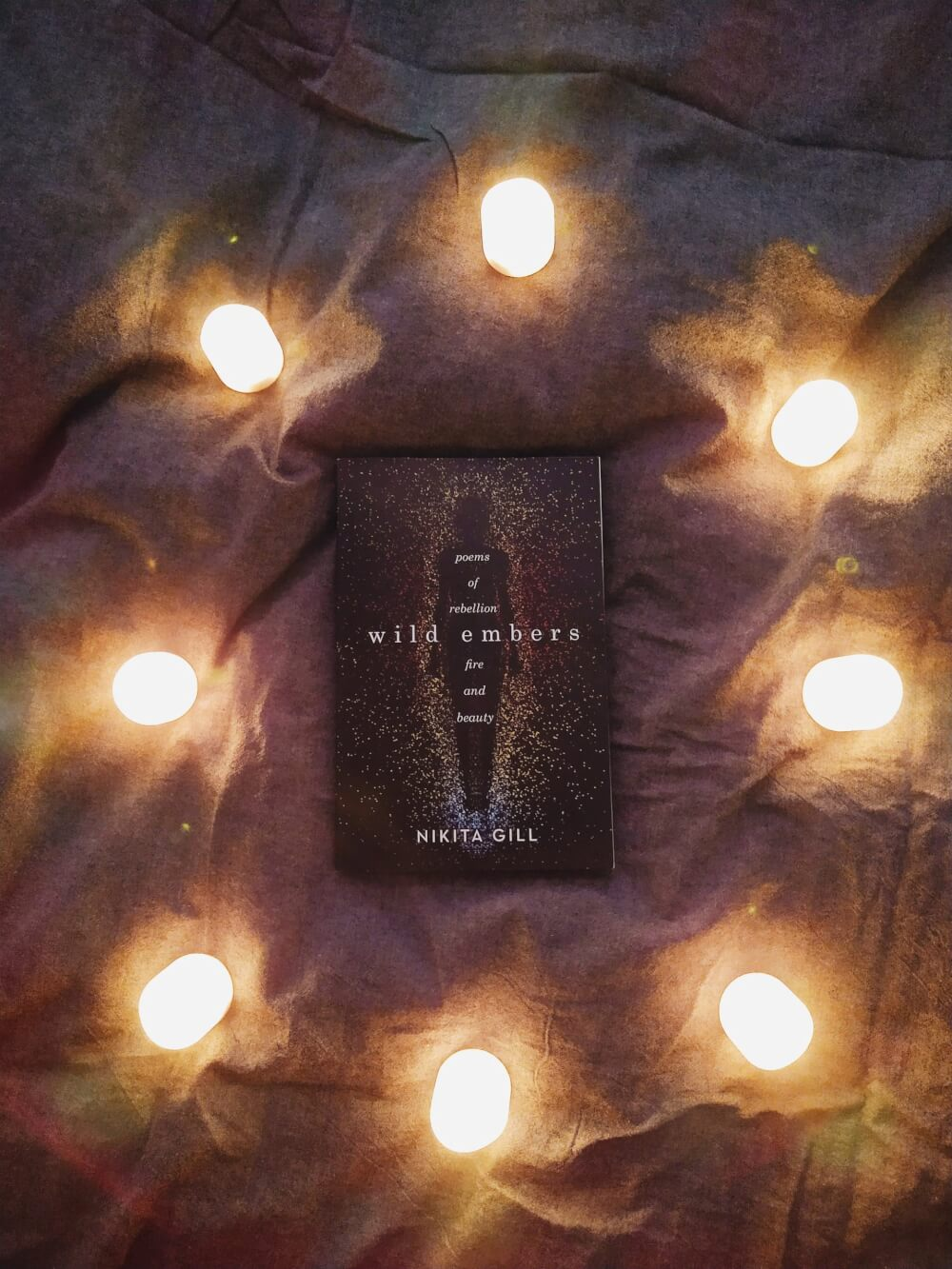 """""""Wild Embers"""" on grey duvet circled by LED candles"""