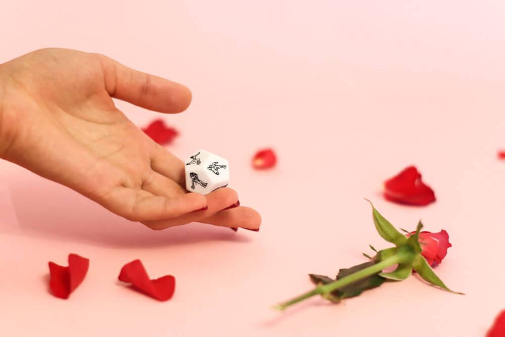 Sex positions hexagonal dice in hand atop pink background where rose petals lay